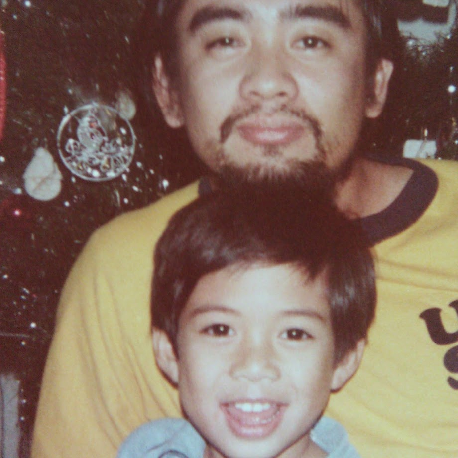 A probably mid to late 30s Filipino Father with a beard and mustache poses in front of a Christmas tree with his son, the author of this post. They have a striking resemblance.